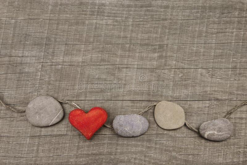 Jeden czerwony serce z kamieniami na drewnianym tle fotografia royalty free