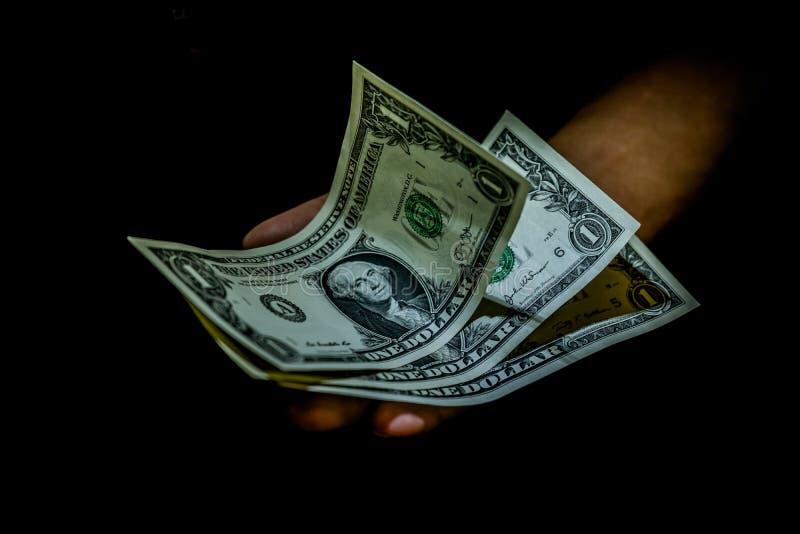 Jeden dolarowi rachunki w ręce osoba odizolowywająca na czerni obrazy royalty free