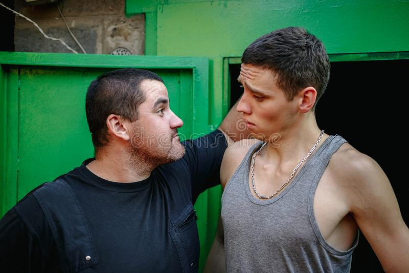 Jeden facet trzyma innego faceta ucho obrazy royalty free