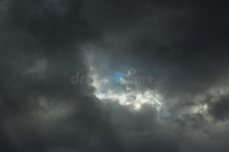 Jeden jaskrawy punktu zmrok chmurnieje z troszeczkę niebieskie niebo obraz stock