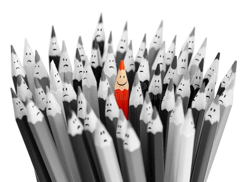 Jeden jaskrawy uśmiechnięty ołówek wśród wiązki szary smutny  obrazy royalty free