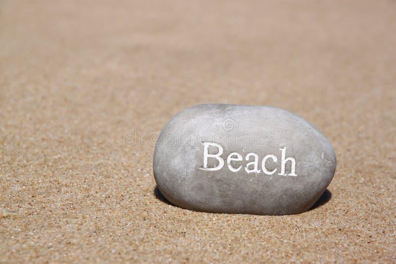 Jeden kamienni otoczaki z słowem wyrzucać na brzeg nad piaskowatą plażą obraz stock
