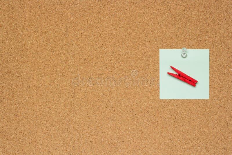 Jeden kolorowe notatki z białymi pushpins i clothespins odizolowywający na korkowym tle zdjęcia stock