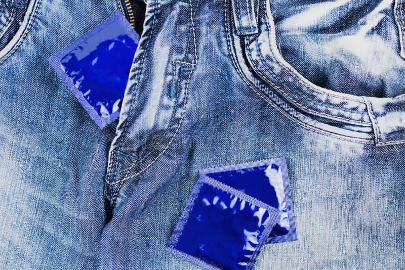 Jeden kondom w suwaczku i dwa kondomach rozpraszał na niebieskich dżinsach obraz stock
