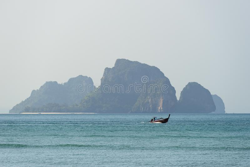 Jeden lokalna łódź żegluje morze w turkusowych wodach przeciw skałom na wyspie w Azja w Tajlandia zdjęcia royalty free