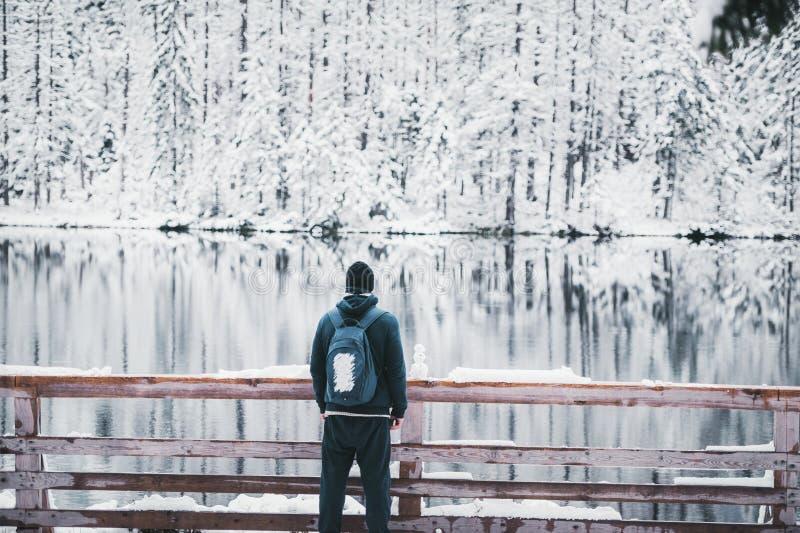 Jeden mężczyzny podróżnika pobyt na śnieżnym halnym jeziorze Mały bałwan jest blisko go widok z powrotem fotografia stock