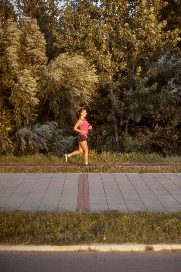 Jeden młoda kobieta, biega samotnego outdoors na asfaltowym śladzie zdjęcie royalty free