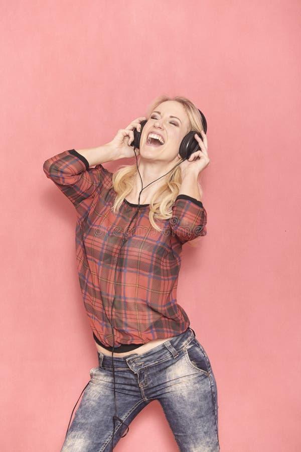 Jeden m?oda kobieta, komicznie roze?miana emocja, krzyczy podczas gdy s?uchaj?cy muzyka na he?mofonach zdjęcie stock