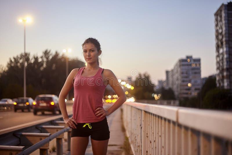 Jeden młoda kobieta, patrzejący kamera, pozujący na moście, jest ubranym sport odziewa zdjęcia royalty free