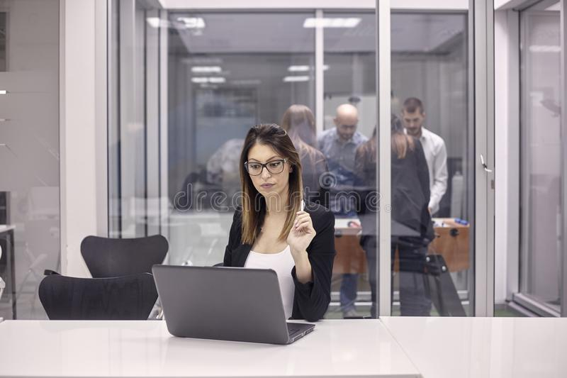 Jeden młoda kobieta pracuje na laptopie w biurze, grupa pracownicy bawić się stołowego futbol w innym biurze zdjęcia stock