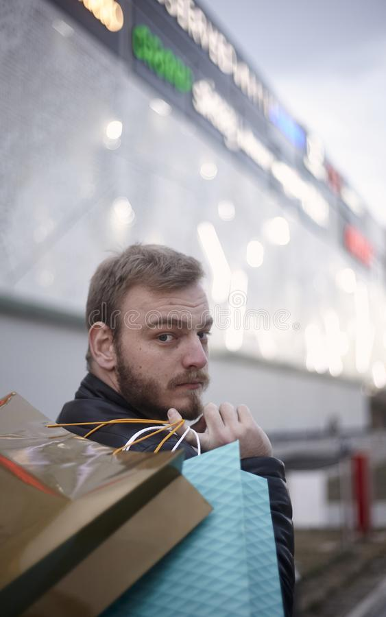 Jeden młody człowiek, 20-29 lat, niesie torby na zakupy na jego z powrotem, przyglądający kamera z powrotem outdoors przed centru zdjęcia stock
