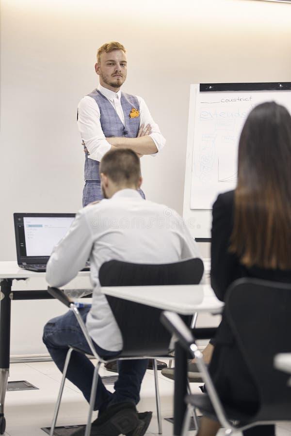 Jeden młody człowiek, 20-29 lat, przedstawia grupa ludzi, zbroi krzyżującego, poważnego wyrażenie w biurze, indoors fotografia stock