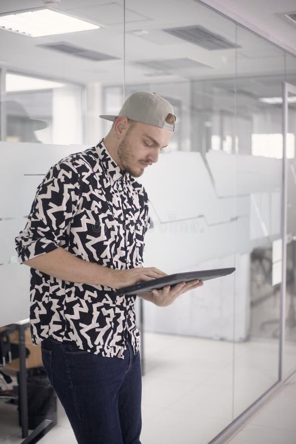Jeden młody człowiek pozycja, 20-29 lat, pracujący w nowożytnej powierzchni biurowej, używać pastylka komputer Przypadkowi ubrani obrazy stock