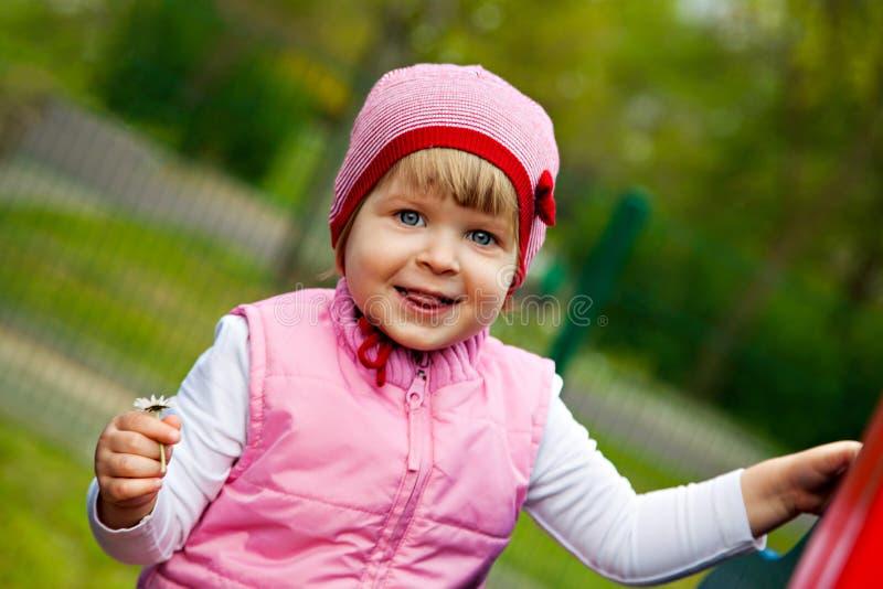 Jeden mała dziewczynka na boisku z kwiatem zdjęcia stock