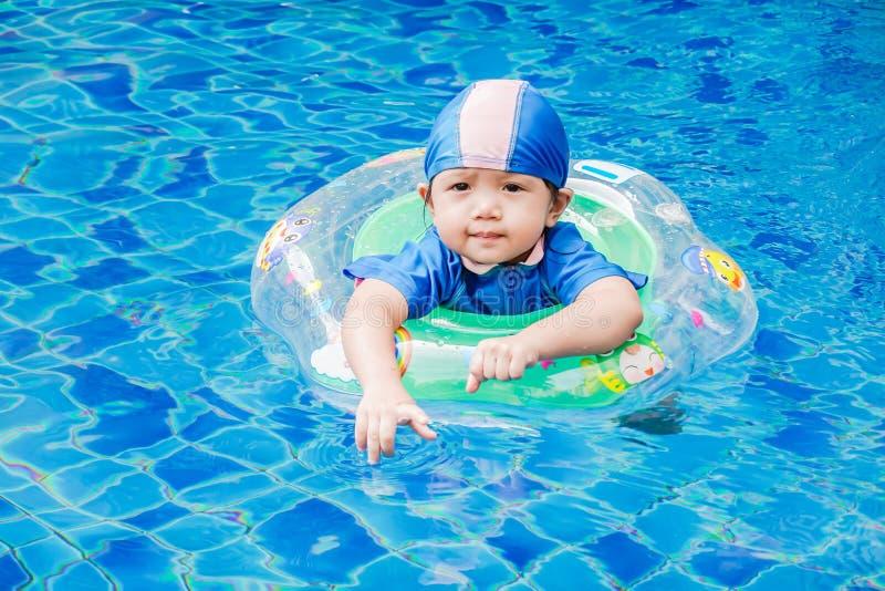 Jeden małe dziewczynki pływa w basenie z gumowym pierścionkiem, mieć f zdjęcie stock