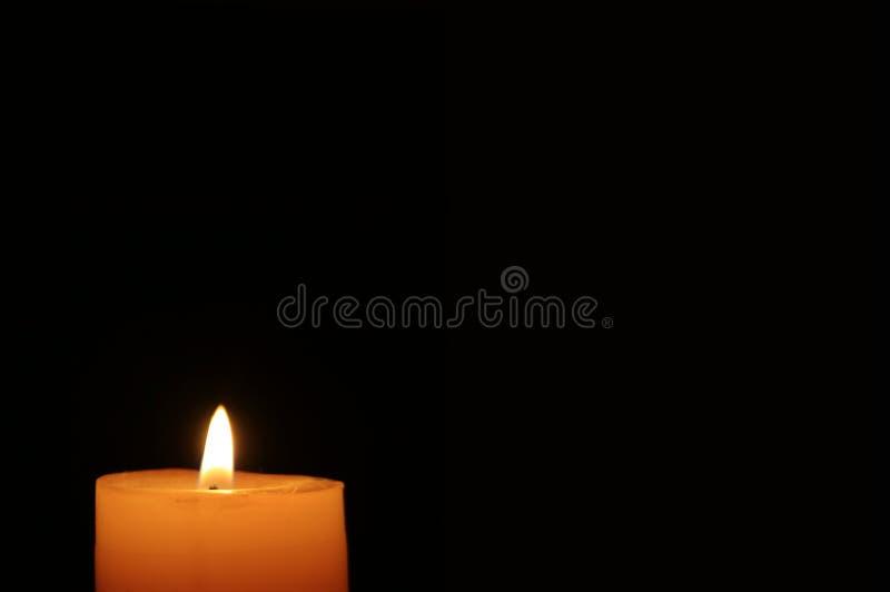 Jeden olśniewająca pomarańczowa kolor świeczka w ciemności obraz stock