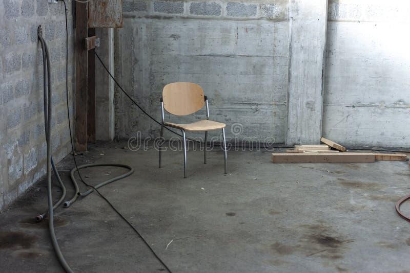 Jeden osamotniony krzesło w kącie zaniechany betonowy budynek obraz royalty free