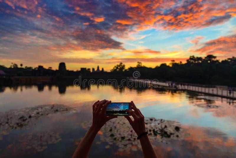Jeden osoba fotografuje Angkor Wat główną fasadową sylwetkę przy jutrzenkowego mienia mądrze telefonem Świat sławna świątynna mas fotografia stock
