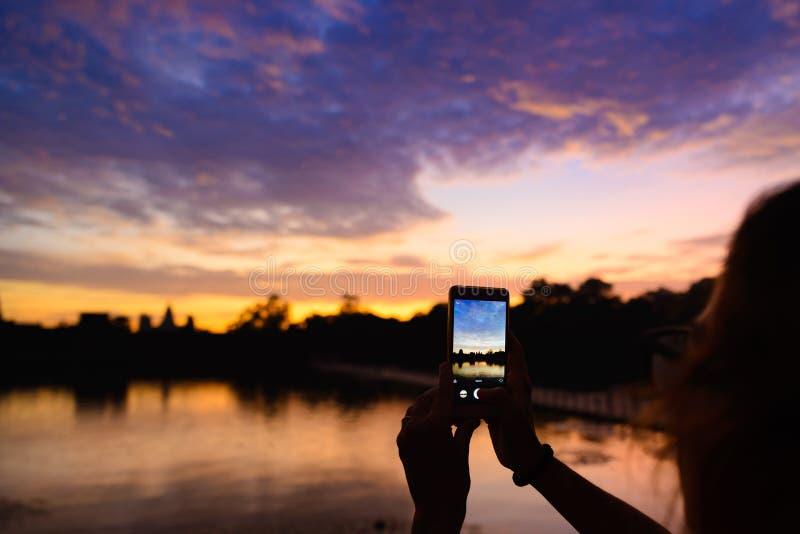 Jeden osoba fotografuje Angkor Wat główną fasadową sylwetkę przy jutrzenkowego mienia mądrze telefonem Świat sławna świątynna mas obraz stock