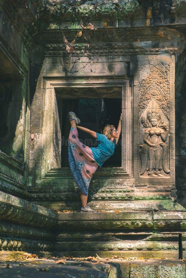 Jeden osoba w Angkor Wat ruinach, podróży miejsce przeznaczenia Kambodża Kobieta w joga pozycji, rozciąga nogę i podnoszącą rękę, obraz stock