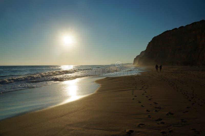 Jeden pary mienie wręcza przespacerowania wzdłuż ocean plaży obrazy stock