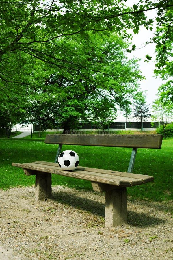 Jeden piłki nożnej piłka na parkowej ławce fotografia royalty free