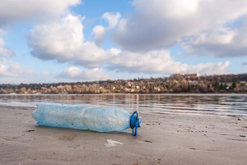 Jeden plastikowa butelka jako dżonka i śmieci na piasek plaży rzucającej w wodnym zanieczyszczaniu środowisko niski punkt i natur fotografia royalty free