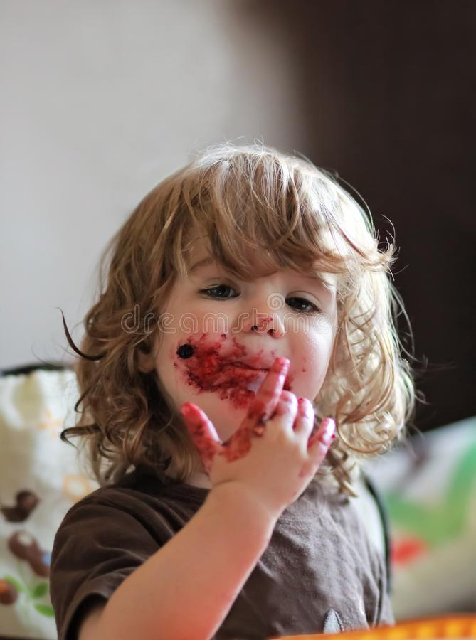 Jeden roczniak dziewczynka je wyśmienicie czarnej jagody i czarnego rodzynku kulebiaka z jej twarzą brudną zdjęcia royalty free