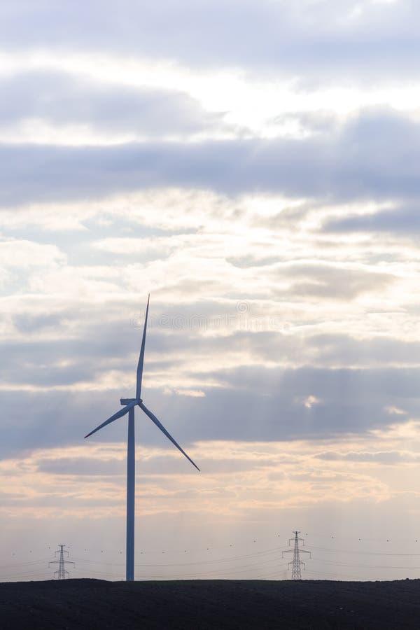 Jeden silnik wiatrowy na rolniczej ziemi z chmurnym niebem w tle zdjęcie royalty free