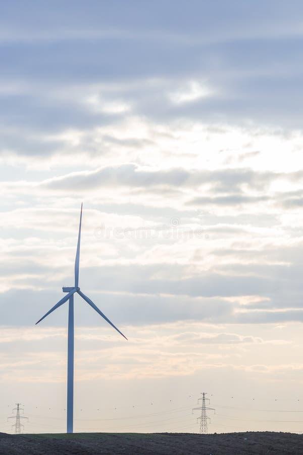 Jeden silnik wiatrowy na rolniczej ziemi z chmurnym niebem w tle zdjęcia royalty free