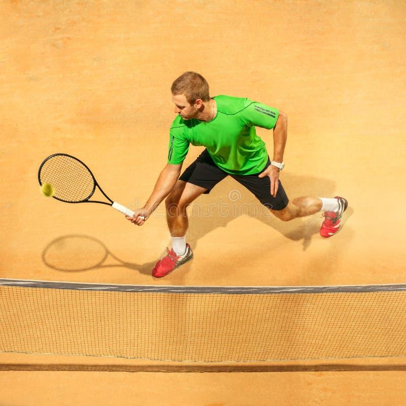 Jeden skokowy gracz, caucasian napadu mężczyzna, bawić się tenisa na earthen sądzie obraz stock