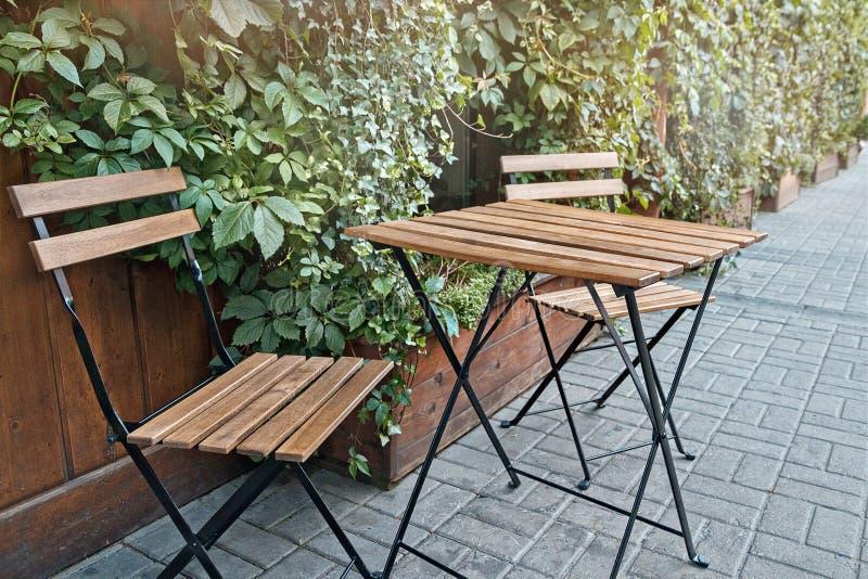 Jeden stół i dwa krzesła od drewnianych desek stojaka na ulicie w miasta s kawiarni w lecie zdjęcia stock