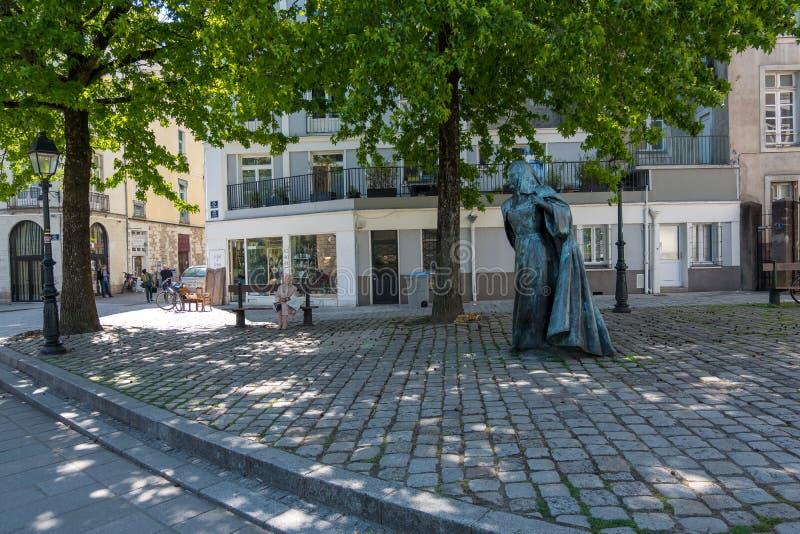 Jeden starszy kobiety obsiadanie na ławce pod zielonymi drzewami zbliża statuę Anne De Bretagne królowa Francja Nantes Francja obraz royalty free