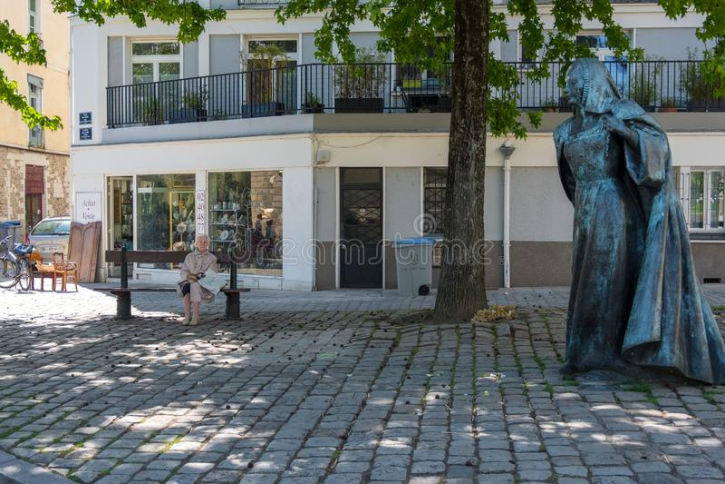 Jeden starszy kobiety obsiadanie na ławce pod zielonymi drzewami zbliża statuę Anne De Bretagne królowa Francja Nantes Francja zdjęcie stock