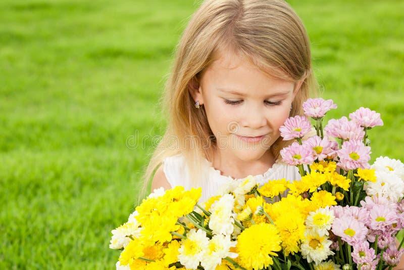 Jeden szczęśliwy małej dziewczynki obsiadanie na trawie z bukietem flo fotografia stock