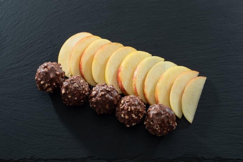 Jedenaście kawałków Pokrojony Apple i Pięć Niegrzeczni Czekoladowi lodów piłek na czerni Krytykowali porcji tacę zdjęcie royalty free
