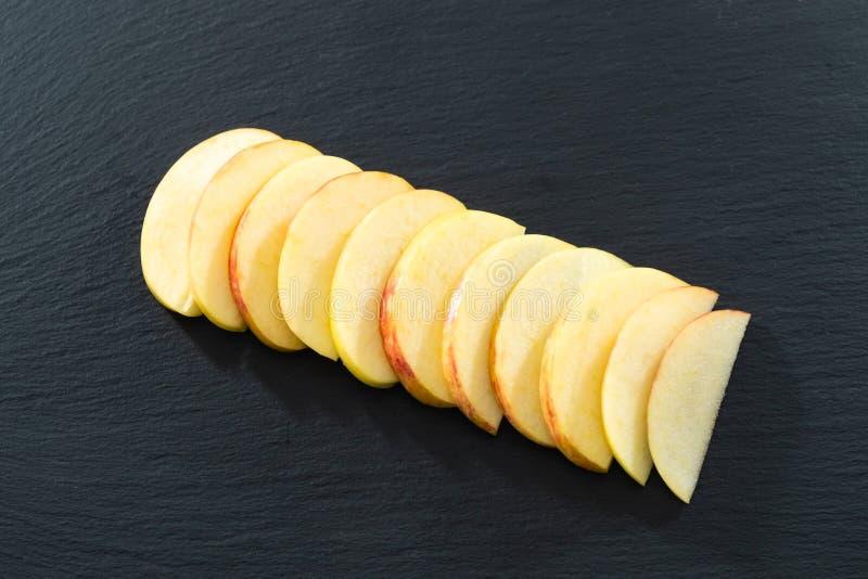 Jedenaście kawałków Pokrojony Apple na czerni Krytykowali porcji tacę fotografia stock