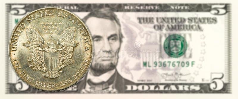 1 jednoczył stanu srebnego dolara monetę przeciw 5 dolara amerykańskiego banknotowi zdjęcie stock