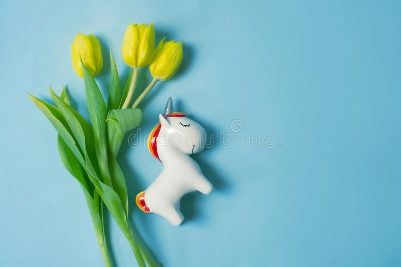 Jednorożec koloru żółtego i postaci tulipany nad pastelowym błękitnym tłem z kopii przestrzenią obraz royalty free