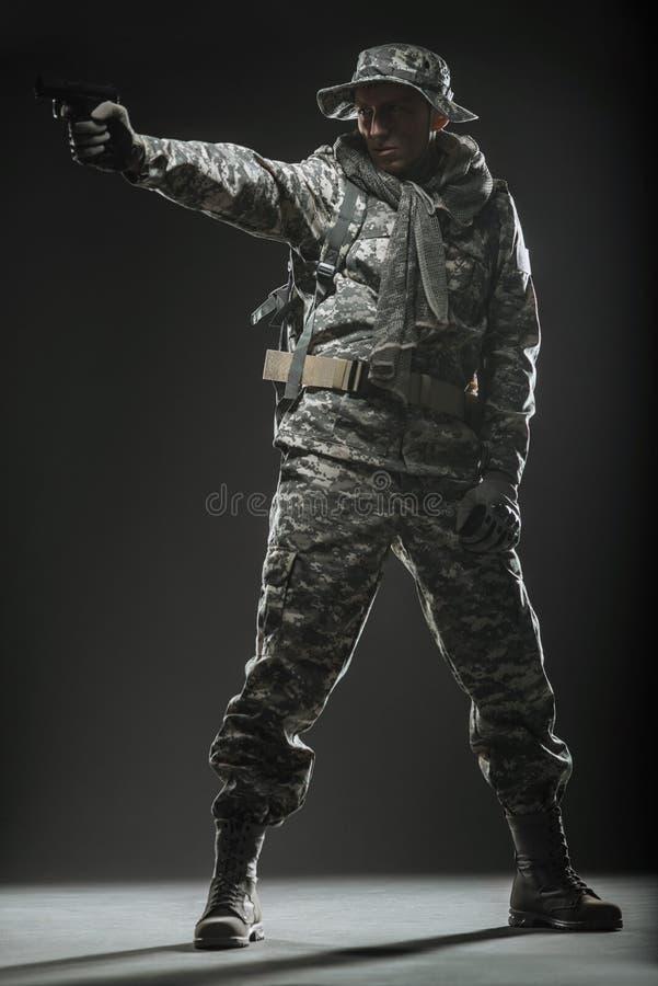 Jednostka specjalna żołnierza mężczyzna z pistoletem na ciemnym tle zdjęcia stock