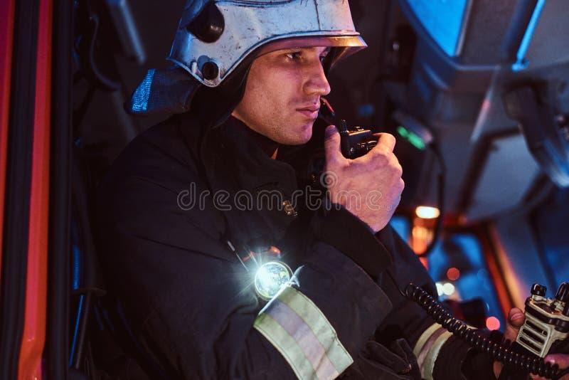 Jednostka straży pożarnej przyjeżdżająca przy porą nocną Palacza obsiadanie w samochodzie strażackim i opowiadać na radiu obrazy royalty free