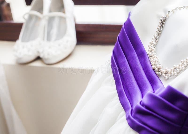 Jedwabnicza Ślubnej sukni i perły kolia z purpurowym faborkiem obrazy royalty free