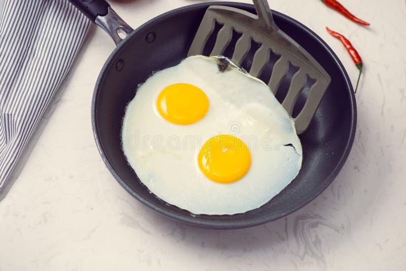Jedzący w procesie, smażący jajka w smaży niecce dla śniadania obraz stock