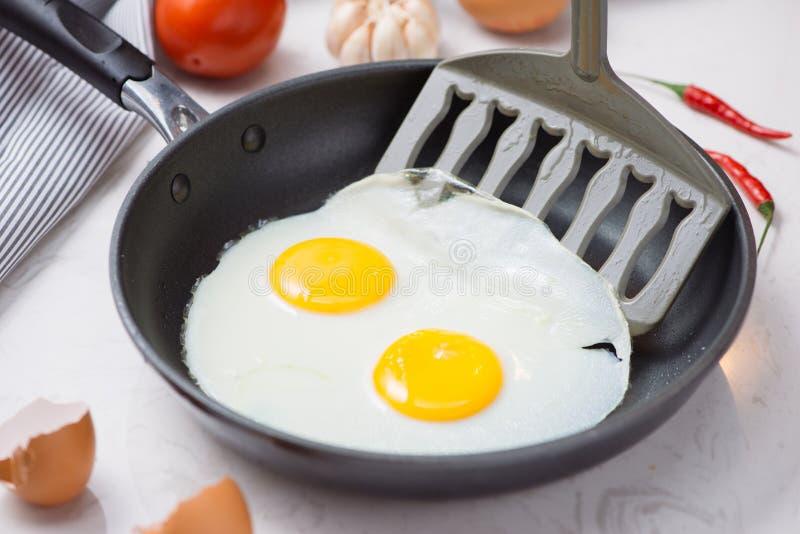 Jedzący w procesie, smażący jajka w smaży niecce dla śniadania fotografia royalty free