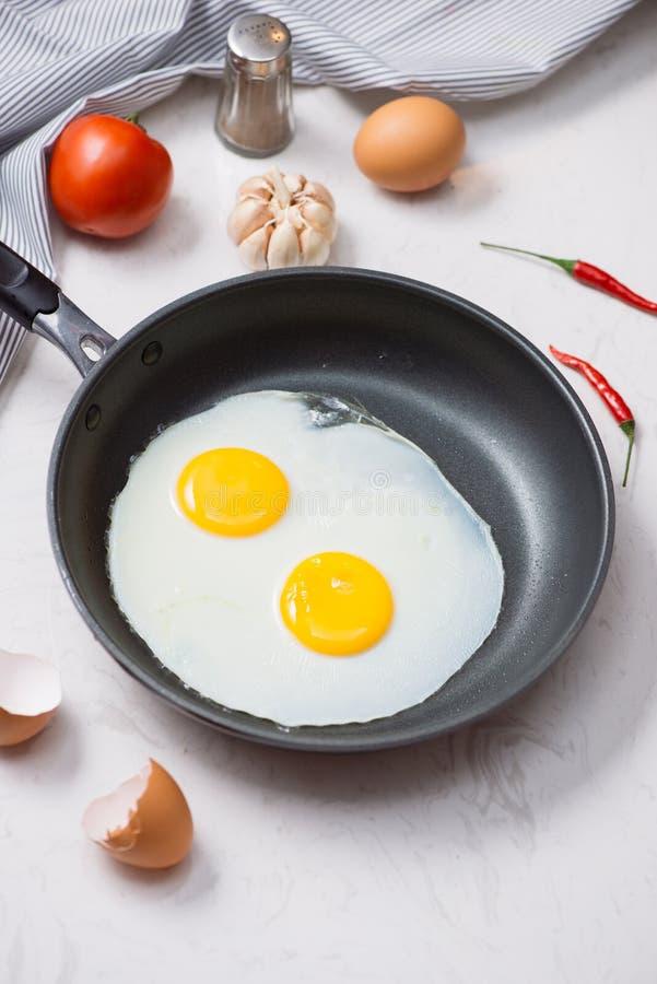 Jedzący w procesie, smażący jajka w smaży niecce dla śniadania na białym tle Światło dzienne zdjęcie stock