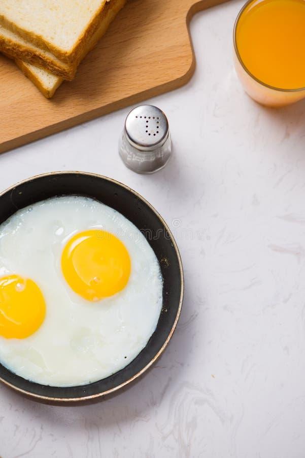 Jedzący w procesie, smażący jajka w smaży niecce, grzanka i lub obrazy royalty free