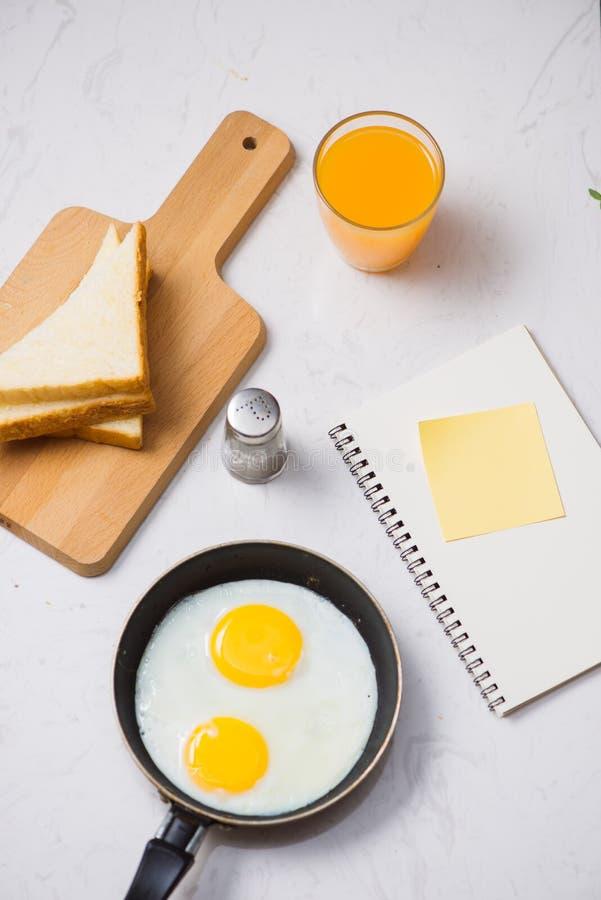 Jedzący w procesie, smażących jajkach w smaży niecce, grzance i soku pomarańczowym dla śniadania na białym tle, Światło dzienne obraz stock