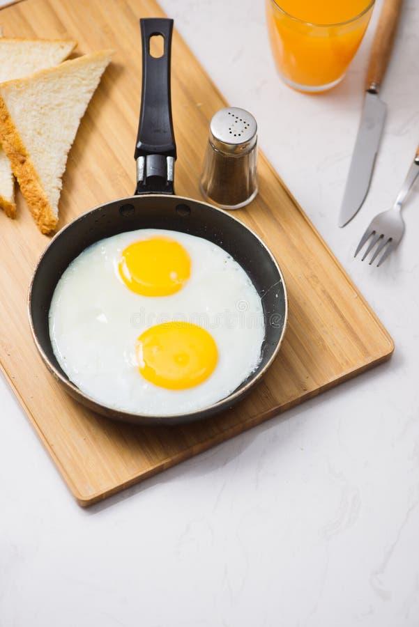 Jedzący w procesie, smażących jajkach w smaży niecce, grzance i soku pomarańczowym dla śniadania na białym tle, Światło dzienne obrazy stock