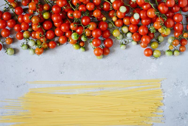 Jedzenie rama Makaronów składników pojęcie Uncooked spaghetti i czereśniowy pomidor na błękitnym tle Odgórny widok z kopii przest zdjęcie stock