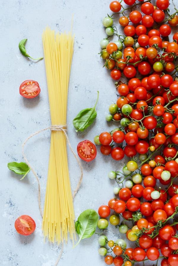 Jedzenie rama Makaronów składników pojęcie Uncooked spaghetti i czereśniowy pomidor z zielonym basilem na błękitnym tle Odgórny w fotografia royalty free